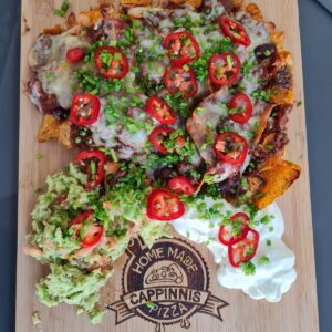 Nachos - Slow cooked beef chilli con carne served on corn crisps, melted cheddar with a zingy guacamole, and sour cream.